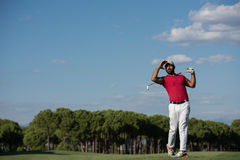 Golf player hitting long shot. Golf player hitting shot with driver on course at beautiful sunny day stock image