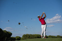 Golf player hitting long shot. Golf player hitting shot with driver on course at beautiful sunny day stock photography