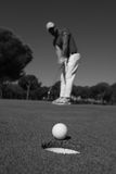 Golf player hitting shot, ball on edge of hole Royalty Free Stock Photos