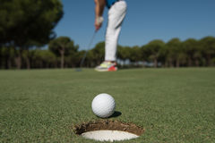 Golf player hitting shot, ball on edge of hole Stock Image