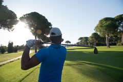 Golf player hitting shot. With club on course at beautiful morning with sun flare in background stock photo