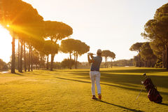 Golf player hitting shot with club. On course at beautiful morning with sun flare in background stock image
