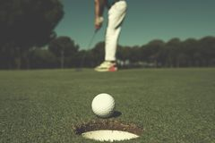Golf player hitting shot, ball on edge of hole. Golf player hitting shot with driver, ball on edge of  hole  on course in background  at beautiful sunny day Royalty Free Stock Photography