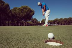Golf player hitting shot, ball on edge of hole. Golf player hitting shot with driver, ball on edge of  hole  on course in background  at beautiful sunny day Stock Images
