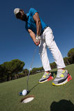 Golf player hitting shot at sunny day, wide angle lens Stock Photo