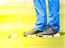 Golf player making the putt. A male golf player putting the golf ball on the green towards the golf course hole Stock Photography