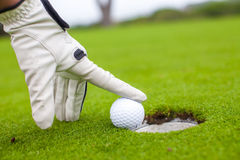 Golf player man pushing golfball into the hole Stock Photo