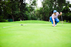 Golf player marking ball on the putting green. Before lifting the ball Royalty Free Stock Photo