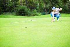 Golf player marking ball on the putting green. Before lifting the ball Stock Images