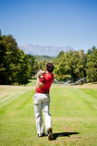 Golf player performs a tee shot. Using a driver club. One young caucasian male golfer, red shirt and white pants. Clear summer day, rear view. Summer outdoor Stock Photography