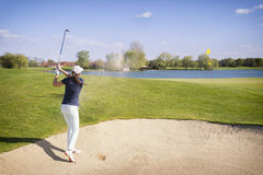 Golf player pitching from bunker. Royalty Free Stock Photos