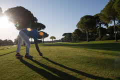 Golf player placing ball on tee Stock Images