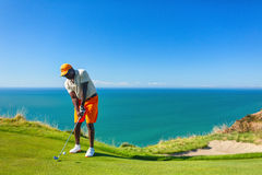 Golf player is practicing on the golf field. Cape Kidnappers golf court. New Zealand. Stock Photos