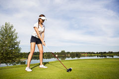 Golf player preparing for teeing off. Girl golf player tee-box focusing on golf ball for teeing off royalty free stock photos