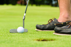 Golf player putting ball in hole. Golf player putting ball into hole, only feet and iron to be seen Stock Images