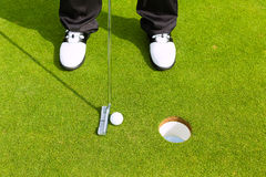 Golf player putting ball in hole. Golf player putting ball into hole, only feet and iron to be seen Stock Photos
