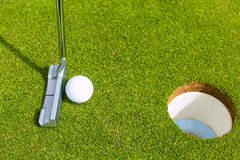 Golf player putting ball in hole. Golf player putting ball into hole, only ball, hole and iron to be seen Royalty Free Stock Photo