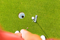 Golf player putting ball in hole. Golf player putting ball into hole, only feet and iron to be seen Stock Photo