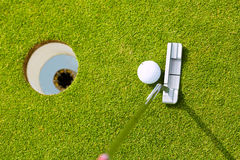 Golf player putting ball in hole. Golf player putting ball into hole, only ball, hole and iron to be seen Stock Photos