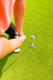 Golf player putting ball in hole. Golf player putting ball into hole, only feet and iron to be seen Royalty Free Stock Image