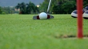 Golf player putting ball into hole, only feet and iron to be seen Royalty Free Stock Image