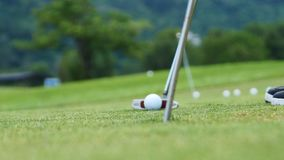 Golf player putting ball into hole, only feet and iron to be seen. Golf player putting ball into hole Stock Photo