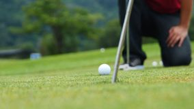 Golf player putting ball into hole, only feet and iron to be seen Royalty Free Stock Photography