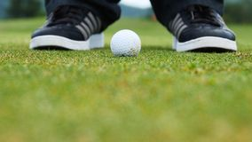 Golf player putting ball into hole, only feet and iron to be seen. Golf player putting ball into hole Royalty Free Stock Photos