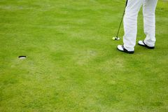 Golf player on putting green Stock Photo