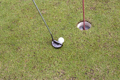 Golf player at the putting green hitting ball into a hole Royalty Free Stock Photography