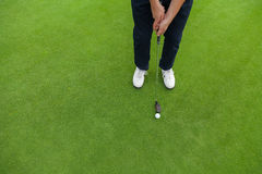 Golf player at the putting green. Hitting ball into a hole Royalty Free Stock Photos
