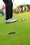 Golf player at the putting green. Hitting ball into a hole Stock Image