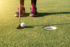 Golf player at the putting green putting golf ball into a hole. Stock Images