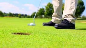 A golf player putting
