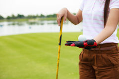 Golf player showing golf ball holding golf club Royalty Free Stock Image