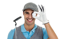 Golf player showing golf ball and holding golf club Stock Photography