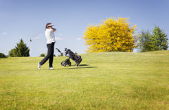 Golf player swinging club on fairway. Active senior female golf player swinging golf club to shoot ball on fairway on beautiful golf course with blue sky in Royalty Free Stock Images