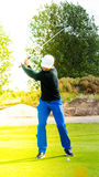 Golf player swinging to shoot Royalty Free Stock Photography