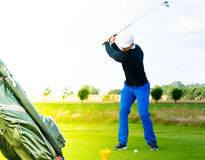 Golf player swinging to shoot Stock Images