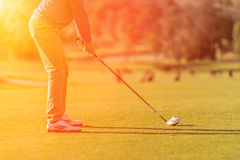 Golf player tee off at sunset Stock Photo