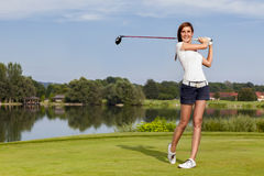 Golf player teeing off. Girl golf player teeing-off with driver from tee-box, front view royalty free stock images