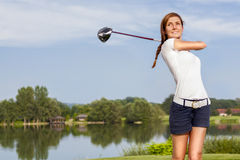 Golf player teeing off. Girl golf player teeing off with driver from tee box, front view royalty free stock photo