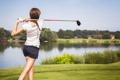 Golf player teeing off. Girl golf player teeing-off from tee-box with driver, view from behind royalty free stock image