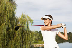 Golf player teeing off. Professional golf player teeing-off with beautiful trees in background, front view royalty free stock photography