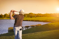 Golf player teeing-off at sunset. Royalty Free Stock Photo