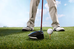 Golf player teeing up to hit ball Stock Photography
