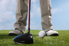 Golf player teeing up to hit ball Stock Images