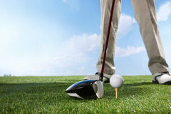 Golf player teeing up to hit ball Royalty Free Stock Photo