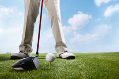 Golf player teeing up to hit ball Royalty Free Stock Photos