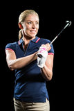 Golf player about to swing a golf ball. On black background Stock Photo